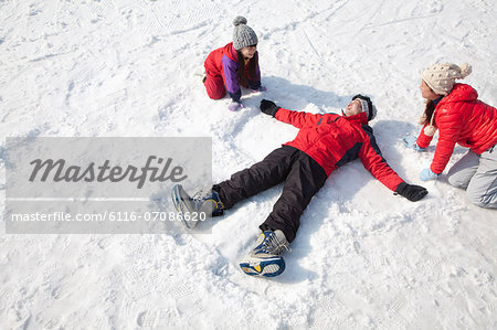 Family Playing in the Snow, Father Making Snow Angel Stock Photo - Premium Royalty-Free, Image code: 6116-07086620