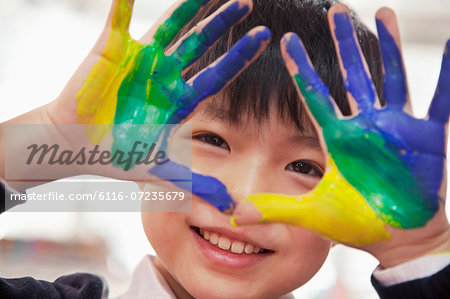 Portrait of smiling schoolboy finger painting, close up on hands Stock Photo - Premium Royalty-Free, Image code: 6116-07235679
