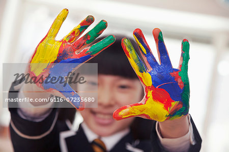 Smiling schoolgirl finger painting, close up on hands Stock Photo - Premium Royalty-Free, Image code: 6116-07235680