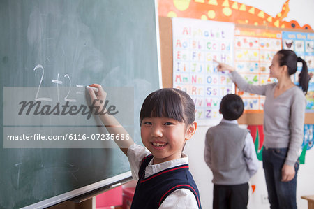 Schoolgirl doing math equation on the black board Stock Photo - Premium Royalty-Free, Image code: 6116-07235686
