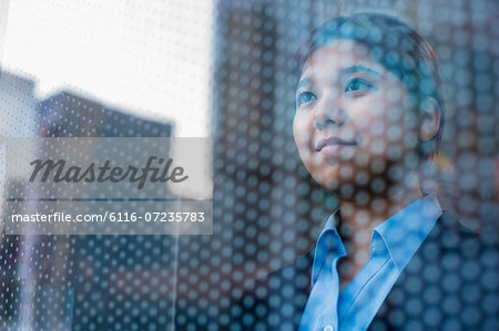Businesswoman looking out through window, reflection of the city on the glass Stock Photo - Premium Royalty-Free, Image code: 6116-07235783