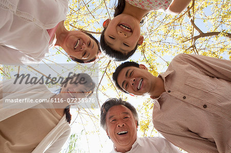 Happy smiling family in a circle looking down in a park in the springtime Stock Photo - Premium Royalty-Free, Image code: 6116-07235876