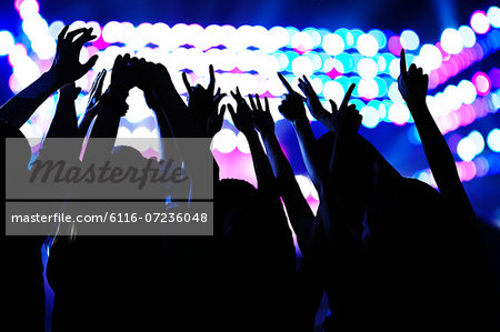 Audience watching a rock show, hands in the air, rear view, stage lights Stock Photo - Premium Royalty-Free, Image code: 6116-07236048