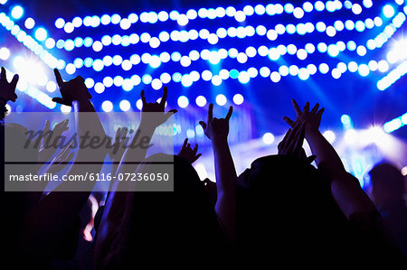 Audience watching a rock show, hands in the air, rear view, stage lights Stock Photo - Premium Royalty-Free, Image code: 6116-07236050