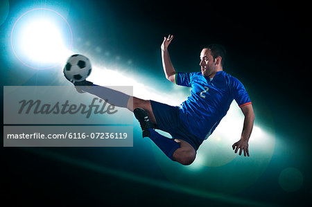 Soccer player in mid air kicking the soccer ball, stadium lights at night in background Stock Photo - Premium Royalty-Free, Image code: 6116-07236119