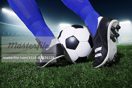 Close up of feet kicking the soccer ball, night time in the stadium Stock Photo - Premium Royalty-Free, Image code: 6116-07236138