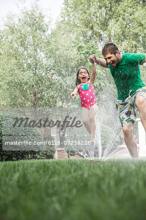 Father holding daughters hand while she jumps through the sprinkler in the garden Stock Photo - Premium Royalty-Free, Image code: 6116-07236226