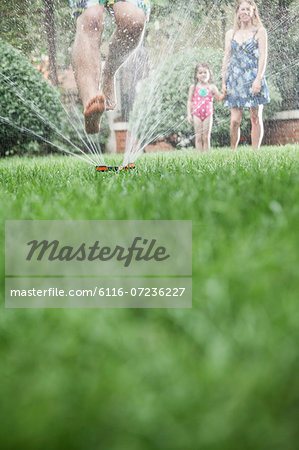 Surface level shot of father jumping through a sprinkler in the grass, mother and daughter watch in the background Stock Photo - Premium Royalty-Free, Image code: 6116-07236227