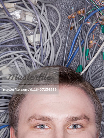 Businessman's face lying down on computer cables looking up, half Stock Photo - Premium Royalty-Free, Image code: 6116-07236259