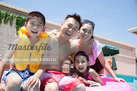 Family portrait, mother, father, daughter, and son, smiling by the pool Stock Photo - Premium Royalty-Free, Image code: 6116-07236312