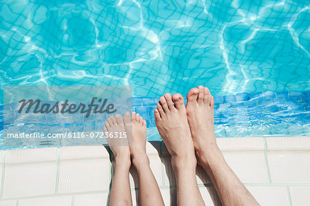 Close up of two people's legs by the pool side Stock Photo - Premium Royalty-Free, Image code: 6116-07236315