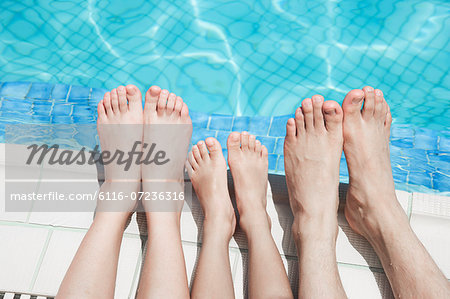 Close up of three people's legs by the pool side Stock Photo - Premium Royalty-Free, Image code: 6116-07236316