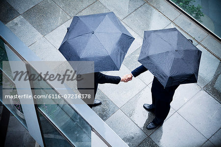 High angle view of two businessmen holding umbrellas and shaking hands in the rain Stock Photo - Premium Royalty-Free, Image code: 6116-07236378