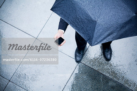 High angle view of businessman holding an umbrella and looking at his phone in the rain Stock Photo - Premium Royalty-Free, Image code: 6116-07236380