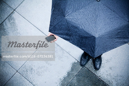 High angle view of businessman holding an umbrella and looking at his phone in the rain Stock Photo - Premium Royalty-Free, Image code: 6116-07236381