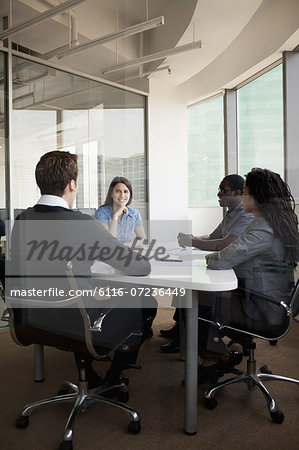 Four business people sitting at a conference table and discussing during a business meeting Stock Photo - Premium Royalty-Free, Image code: 6116-07236449