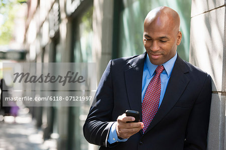 Business People. A Businessman In A Suit And Red Tie, Checking His Phone. Stock Photo - Premium Royalty-Free, Image code: 6118-07121997