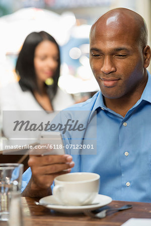 Business People. Two People Sitting At Coffee Shop Tables, Checking Their Messages. Stock Photo - Premium Royalty-Free, Image code: 6118-07122001