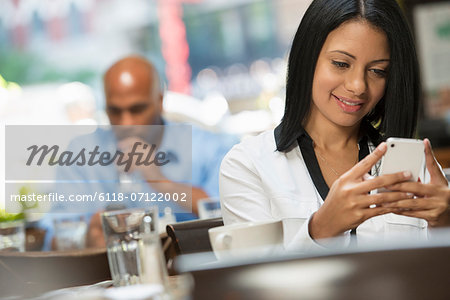 Business People. Two People Sitting At Coffee Shop Tables, Checking Their Messages. Stock Photo - Premium Royalty-Free, Image code: 6118-07122002