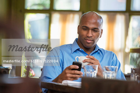 Business People. A Man Sitting Checking His Phone. Stock Photo - Premium Royalty-Free, Image code: 6118-07122004