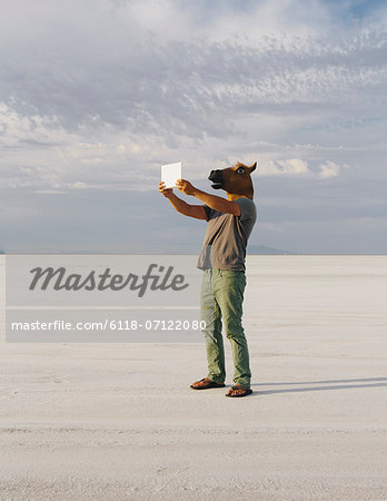 A Man Wearing A Horse Mask, Taking A Photograph With A Tablet Device, On Bonneville Salt Flats. Stock Photo - Premium Royalty-Free, Image code: 6118-07122080