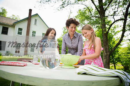 A Summer Family Gathering At A Farm. A Woman And Two Children Standing Outside By A Table, Laying The Table. Making Lemonade. Stock Photo - Premium Royalty-Free, Image code: 6118-07122147