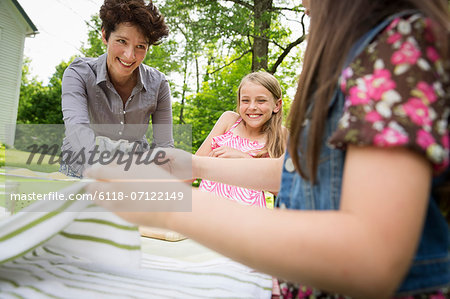 A Summer Family Gathering At A Farm. A Woman And Two Children Standing Outside By A Table, Laying The Table. Stock Photo - Premium Royalty-Free, Image code: 6118-07122149