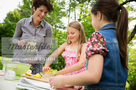 A Summer Family Gathering At A Farm. A Woman And Two Children Standing Outside By A Table, Laying The Table. Making Lemonade. Stock Photo - Premium Royalty-Free, Image code: 6118-07122151