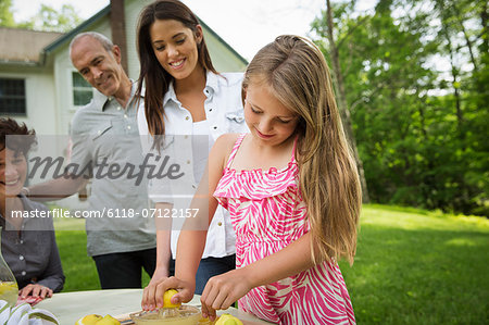 A Summer Family Gathering At A Farm. A Girl Slicing And Juicing Lemons To Make Lemonade. Stock Photo - Premium Royalty-Free, Image code: 6118-07122157
