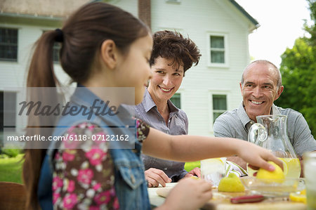 A Summer Family Gathering At A Farm. A Family Group, Parents And Children. Making Fresh Lemonade. Stock Photo - Premium Royalty-Free, Image code: 6118-07122162