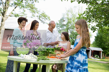 Family Party. Five People Gathered Around A Table Preparing Fresh Salads And Fruit For A Party. Two Girls, One Young Woman And A Mature Couple. Stock Photo - Premium Royalty-Free, Image code: 6118-07122183