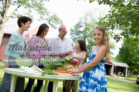 Family Party. A Table Laid With Salads And Fresh Fruits And Vegetables. Parents And Children. Two Girls, One Young Woman And A Mature Couple. Stock Photo - Premium Royalty-Free, Image code: 6118-07122184