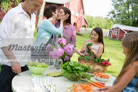 Family Party. A Table Laid With Salads And Fresh Fruits And Vegetables. Parents And Children. A Mother Kissing A Daughter On The Cheek. Stock Photo - Premium Royalty-Free, Image code: 6118-07122187