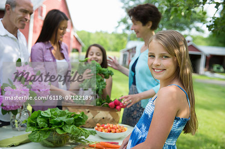 Family Party. A Table Laid With Salads And Fresh Fruits And Vegetables. Parents And Children. Stock Photo - Premium Royalty-Free, Image code: 6118-07122189