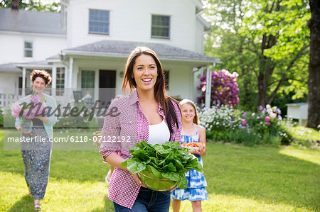 Family Party. Parents And Children Walking Across The Lawn Carrying Flowers, Fresh Picked Vegetables And Fruits. Preparing For A Party. Stock Photo - Premium Royalty-Free, Image code: 6118-07122192