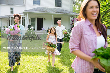 Family Party. Parents And Children Walking Across The Lawn Carrying Flowers, Fresh Picked Vegetables And Fruits. Preparing For A Party. Stock Photo - Premium Royalty-Free, Image code: 6118-07122193