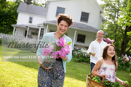 Family Party. Parents And Children Walking Across The Lawn Carrying Flowers, Fresh Picked Vegetables And Fruits. Preparing For A Party. Stock Photo - Premium Royalty-Free, Image code: 6118-07122194