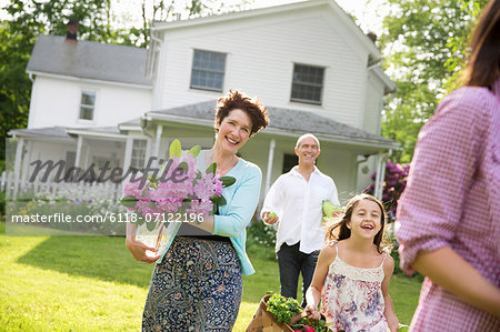 Family Party. Parents And Children Walking Across The Lawn Carrying Flowers, Fresh Picked Vegetables And Fruits. Preparing For A Party. Stock Photo - Premium Royalty-Free, Image code: 6118-07122196