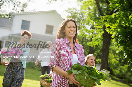 Family Party. Parents And Children Walking Across The Lawn Carrying Flowers, Fresh Picked Vegetables And Fruits. Preparing For A Party. Stock Photo - Premium Royalty-Free, Image code: 6118-07122198
