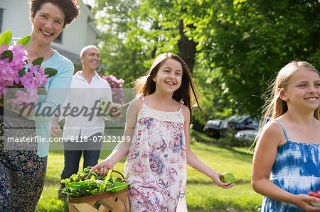 Family Party. Parents And Children Walking Across The Lawn Carrying Flowers, Fresh Picked Vegetables And Fruits. Preparing For A Party. Stock Photo - Premium Royalty-Free, Image code: 6118-07122199