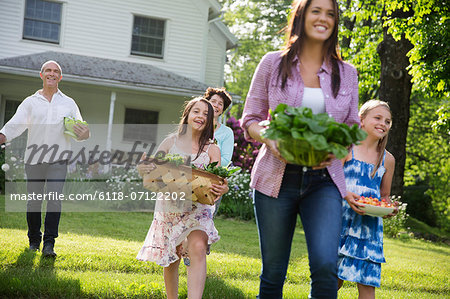 Family Party. Parents And Children Walking Across The Lawn Carrying Flowers, Fresh Picked Vegetables And Fruits. Preparing For A Party. Stock Photo - Premium Royalty-Free, Image code: 6118-07122202