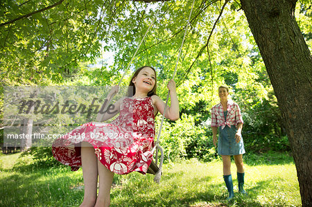Summer. A Girl In A Sundress On A Swing Under A Leafy Tree. A Woman Standing Behind Her. Stock Photo - Premium Royalty-Free, Image code: 6118-07122206