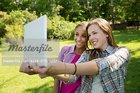 Two Girls Sitting Outdoors On A Bench, Using A Digital Tablet. Holding It Out At Arm's Length. Stock Photo - Premium Royalty-Free, Image code: 6118-07122217