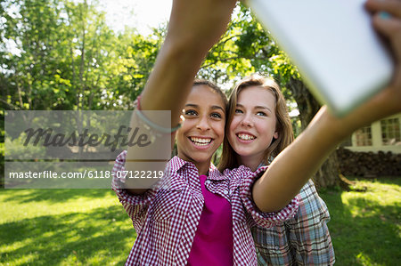 Two Girls Sitting Outdoors On A Bench, Using A Digital Tablet. Holding It Out At Arm's Length. Stock Photo - Premium Royalty-Free, Image code: 6118-07122219