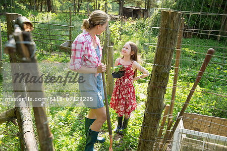 A Woman And A Child Standing At The Open Gate Of A Fenced Enclosure. A Girl Holding A Small Plant In A Pot. Stock Photo - Premium Royalty-Free, Image code: 6118-07122225
