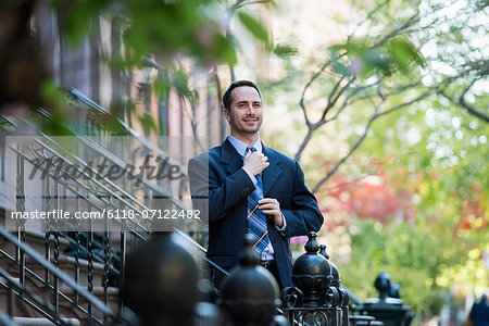 A Man In A Business Suit Adjusting His Tie. At The Bottom Of The Steps Of A Townhouse In A Terrace. Stock Photo - Premium Royalty-Free, Image code: 6118-07122482