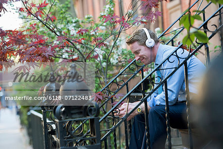 A Man In A Blue Shirt Wearing Headphones And Listening To A Music Player. Stock Photo - Premium Royalty-Free, Image code: 6118-07122483