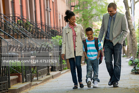 A Family Outdoors In The City. Two Parents And A Young Boy Walking Together. Stock Photo - Premium Royalty-Free, Image code: 6118-07122526