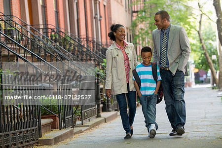 A Family Outdoors In The City. Two Parents And A Young Boy Walking Together. Stock Photo - Premium Royalty-Free, Image code: 6118-07122527