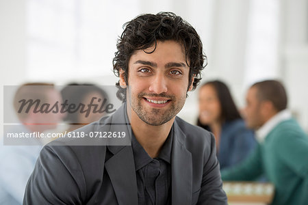 Business Meeting. A Group Sitting Down Around A Table. A Man Smiling Confidently. Stock Photo - Premium Royalty-Free, Image code: 6118-07122619